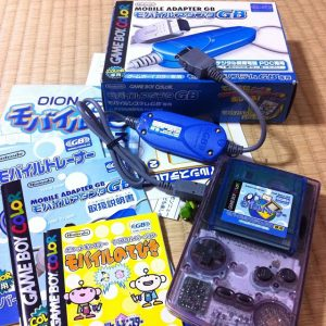 Image of the contents included in the Japan-only Mobile Adapter GB's package, including the adapter itself, a cartridge for Mobile Trainer, and instruction manuals and leaflets.